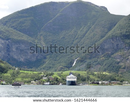 view of Flåm from the water in the fjords; cruiseship; waterfall