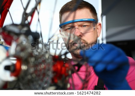 Portrait of skilled mechanic male repairing damaged bike. Concentrated craftsman fixing bicycle with special instrument. Technical expertise and vehicle concept #1621474282