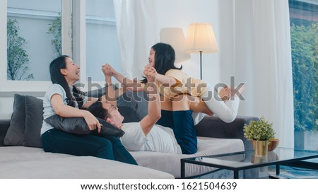 Happy young Asian family play together on couch at home. Chinese mother father and child daughter enjoying happy relax spending time together in modern living room in evening. Royalty-Free Stock Photo #1621504639