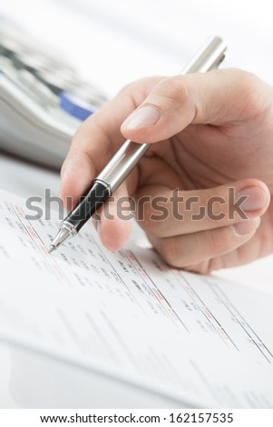Finger is pressing calculator button on chart #162157535