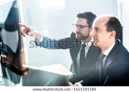 Image of two thoughtful businessmen looking at data on multiple computer screens, solving business issue at business meeting in modern corporate office. Business success concept. #1621581586