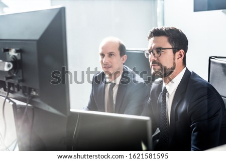 Image of two thoughtful businessmen looking at data on multiple computer screens, solving business issue at business meeting in modern corporate office. Business success concept. #1621581595