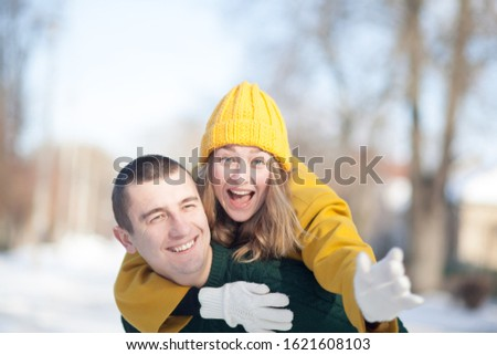 Portrait of a young happy couple. The girl laughs and is very happy. The guy is laughing. Outside, snowy and sunny weather. #1621608103