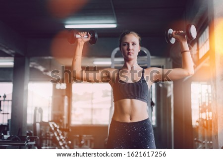 Young fitness woman execute exercise with exercise-machine in gym, horizontal photo.Doing Workout Exercises.Relaxing After Fitness Training in gym.Sports concept fat burning,wellness and healthy. #1621617256