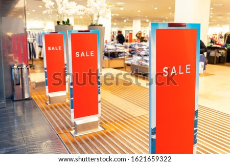 Red bright sale banner on anti-thieft gate sensor at retail shopping mall entrance. Seasonal discount offer in store