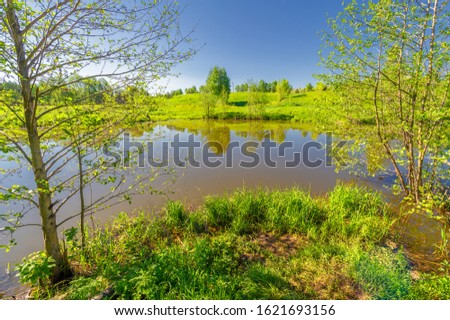 The lake is a large body of water surrounded by land. Walnut and pine trees grow along the edge, complete calm, beautiful hatching in the water #1621693156