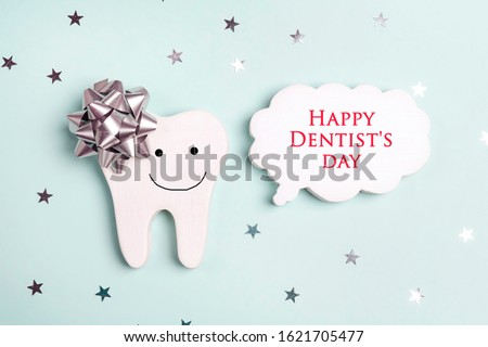 Dentist's Day greeting card with smiling tooth and speech bubble on a blue background. Copy space for text.