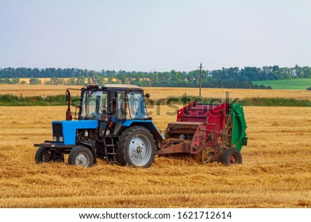 A tractor with a trailed bale making machine collects straw rolls in the field and makes round large bales #1621712614