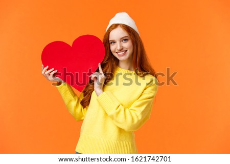Relationship, boyfriend girlfriend and love concept. Cheerful lovely redhead girl holding big red heart sign and smiling, express affection, showing true-feelings to loved partner, orange background #1621742701