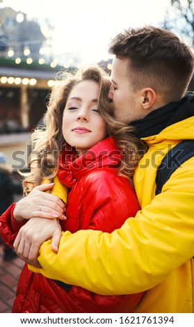 young man in yellow down jacket embracing his girlfriend, spending time together in the city, having a date. urban romantic portrait. Romantic, love and Valentine's Day concept. #1621761394
