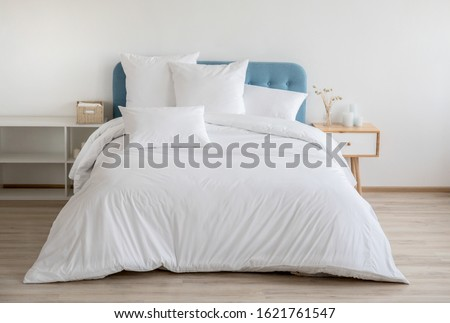 Interior with white bed linen on the sofa. Bedroom with bed, white bedding, and bedside table. White pillows, duvet and duvet case on bed with blue headboard. Front view. #1621761547