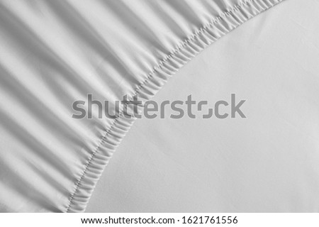 Bed corner with white fitted sheet. White sheet with elastic band. Bed cover close up photo. #1621761556