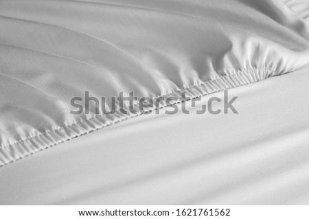 Bed corner with white fitted sheet. White sheet with elastic band. Bed cover. Royalty-Free Stock Photo #1621761562