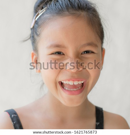 portrait of a happy smiling beautiful and confident child girl, laughing child expressive facial expressions, space for text, joy on the kid face on a light background, fun and joyful concept #1621765873