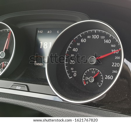 Dusty dashboard of a car showing the fuel gauge and the speedometer while travelling at high speed #1621767820