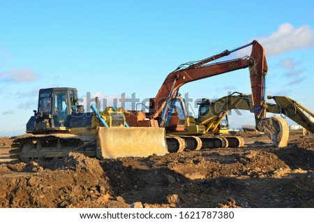 Excavators and dozer digs ground at a construction site for installing sewer storm pipes. Backhoe for digging pipeline ditch. Commercial and Public Civil Work Contracting, trenching, tamps soil #1621787380