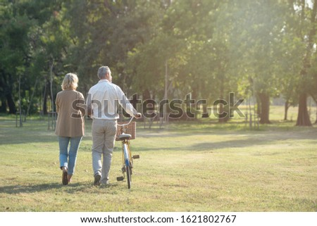 Cheerful active senior couple with bicycle walking through park together. Perfect activities for elderly people in retirement lifestyle. #1621802767