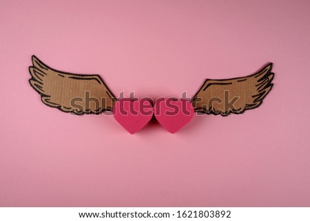 Two pink hearts on the pink background. Cartoon wings connected to the hearts. Love symbol. St Valentines day concept.