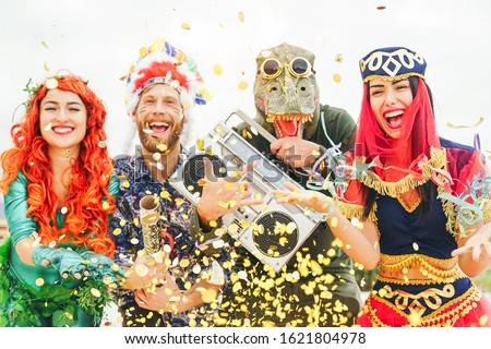 Happy friends celebrating carnival party event outdoor - Young crazy people having fun wearing costumes listening music with vintage boombox stereo - Youth trendy holidays culture lifestyle concept