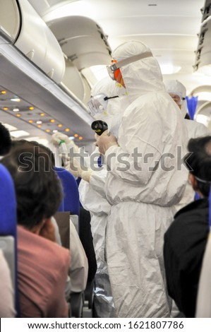 Medics in white hazmat protective suits checking and scanning passengers in a plane for epidemic virus symptoms. Chinese new Wuhan coronavirus illustration. #1621807786