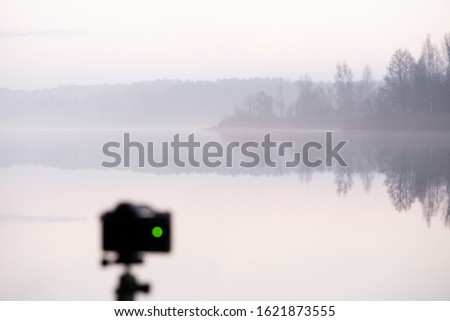 Mirrorless camera on a tripod. Taking pictures by the lake at twilight