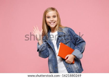 Smiling little kid girl 12-13 years old in denim jacket isolated on pastel pink background. Childhood lifestyle concept. Mock up copy space. Hold notebook waving greeting with hand as notices someone #1621880269
