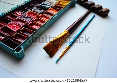 Set of watercolor paints and paintbrushes for painting closeup. Selective focus. #1621884559