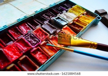 Set of watercolor paints and paintbrushes for painting closeup. Selective focus. #1621884568