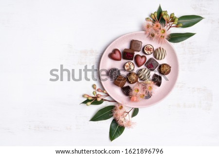 A plate of assorted vegan chocolate confectionery, surrounded by native Australian eucalyptus leaves and gum nuts, on a white background. Can be a gift for Valentines day, Anniversary or Mothers day. #1621896796