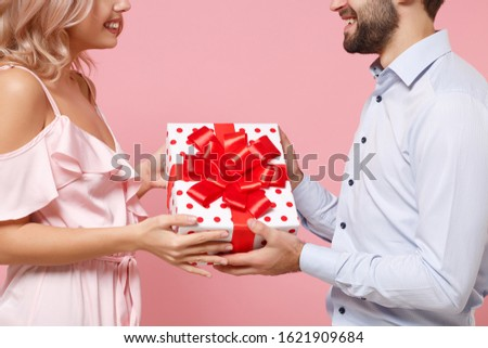 Cropped image of young couple two guy girl in party outfit celebrating isolated on pastel pink background. Valentine's Day Women's Day birthday holiday concept. Hold present box with gift ribbon bow