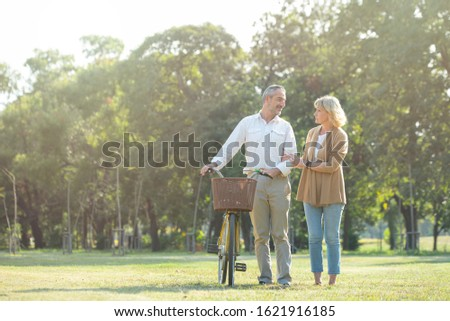 Cheerful active senior couple with bicycle walking through park together. Perfect activities for elderly people in retirement lifestyle. #1621916185