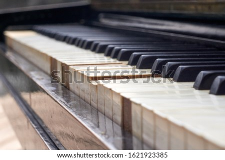 Close up shot of the old piano keyboard. Some keyboard are broken. The piano are black and keyboards have damage. #1621923385