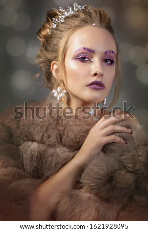 Luxurious girl with a beautiful make-up in a fur coat. Beauty in furs. Model on a bokeh background. Young beautiful woman.Violet makeup. #1621928095