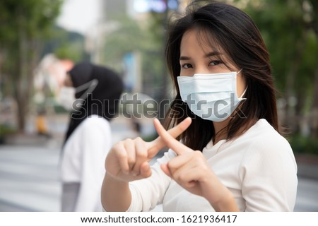 sick woman wearing mask, stopping virus outbreak; concept of biohazard, preventive health care, coronavirus outbreak control, social distancing, physical distancing, personal distancing in public Royalty-Free Stock Photo #1621936417