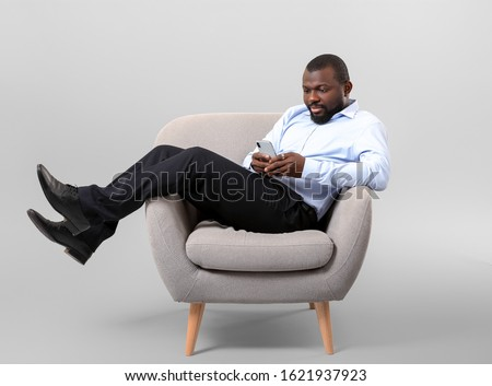 African-American man with mobile phone relaxing in armchair against grey background #1621937923