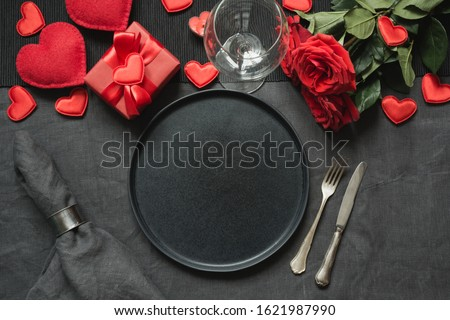 Valentine's day or birthday romantic dinner. Romantic table setting with champagne, red rose on black linen tablecloth. View from above. #1621987990