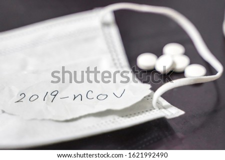 """Novel coronavirus disease named """"2019-nCoV"""" handwriting on paper with breathing mask and pill,selective focus on handwriting text. #1621992490"""