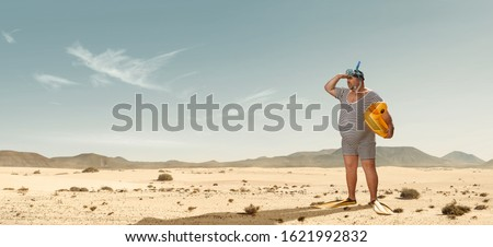 Funny overweight swimmer looking for the beach  in the middle of the desert with copy space Royalty-Free Stock Photo #1621992832