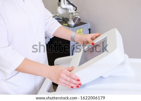 Rear view of a female beautician in white coat presses on display of device to select desired procedure. Concept of modern high-tech equipment for anti-aging procedures. medical examination of patient #1622006179