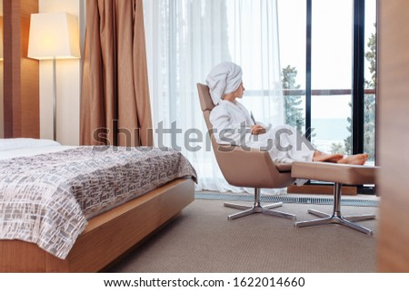 Pleased positive young beautiful girl resting after taking bath sitting on couch in white coat and towel on head looking out of large window overlooking nature. Concept weekend alone rest from society #1622014660