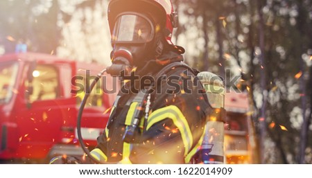 Firefighter in fire fighting operation, fireman in protective clothing and helmet with equipment in action fighting #1622014909
