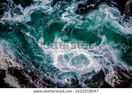 Waves of water of the river and the sea meet each other during high tide and low tide. Whirlpools of the maelstrom of Saltstraumen, Nordland, Norway #1622018047