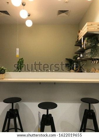Bright dining room interior with white kitchen island and wooden barstools standing in front the black chair #1622019655