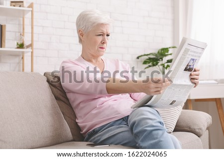 Bad sight problem. Senior lady squinting and holding newspaper far from eyes at home, free space Royalty-Free Stock Photo #1622024065