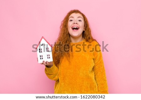 young red head woman looking happy and pleasantly surprised, excited with a fascinated and shocked expression with a house model #1622080342