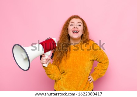 young red head woman looking happy and pleasantly surprised, excited with a fascinated and shocked expression with a megaphone #1622080417