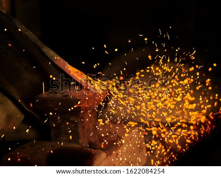 Forge fire in furnace. Blacksmith tempers a steel product in a stove. Smithy forging for hardening and heating iron. Blacksmith stove #1622084254