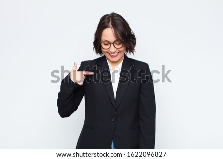 young businesswoman smiling cheerfully and casually, looking downwards and pointing to chest against white wall #1622096827