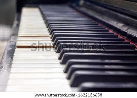 Close up shot of the old piano keyboard. Some keyboard are broken. The piano are black and keyboards have damage. #1622136658
