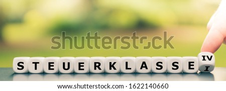 """Hand turns a dice and changes the German expression """"Steuerklasse I"""" (""""German tax class 1"""") to (""""Steuerklasse IV"""" (""""German tax class 4""""), #1622140660"""